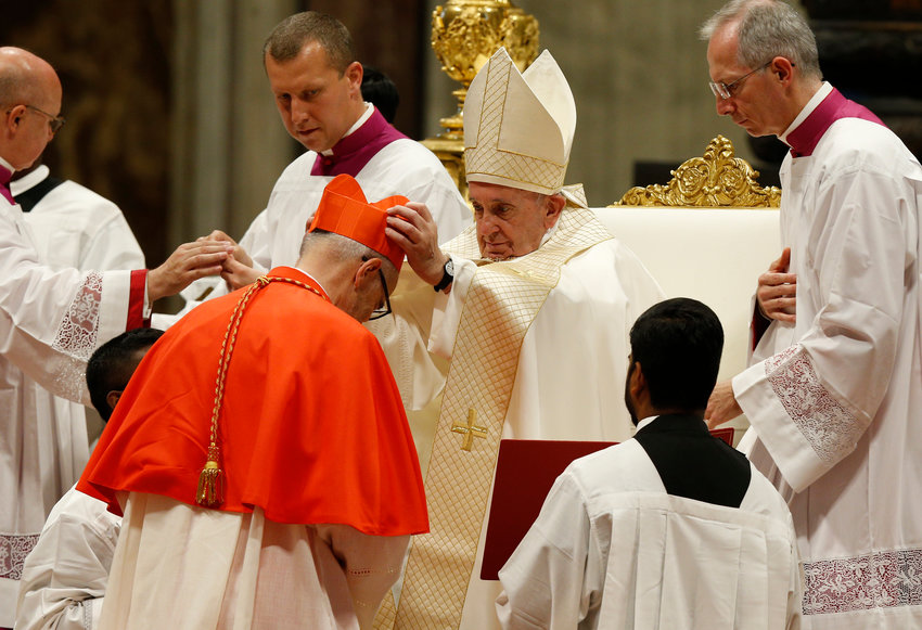 Pope Francis places a red biretta on new Canadian Cardinal Michael Czerny during a consistory for the creation of 13 new cardinals in St. Peter's Basilica at the Vatican Oct. 5, 2019.