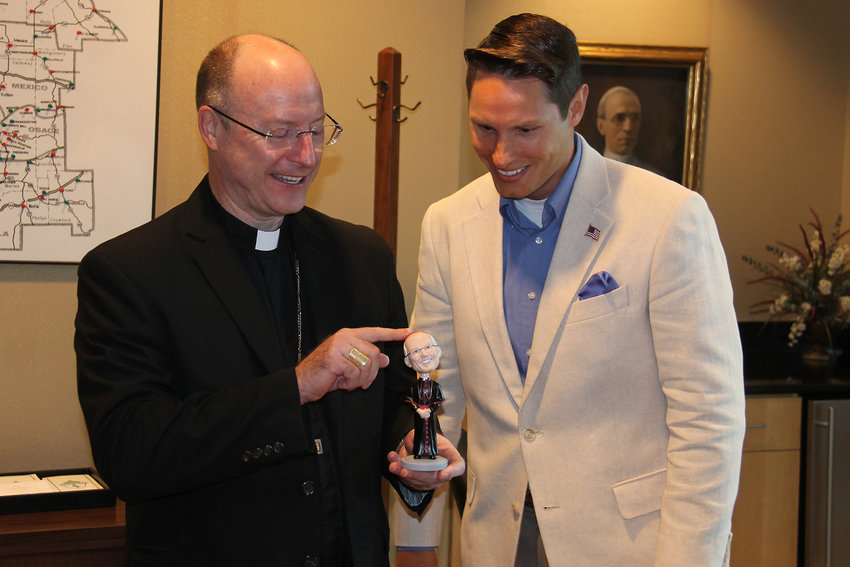 Bishop W. Shawn McKnight checks out one of two bobblehead dolls created in his likeness for a vocations fundraiser by Columbia's Knights of Columbus councils. With him to present the agreeable statuette, along with a monetary donation from the event's proceeds, is Tim Vargesko, grand knight of Knights Council 1529 in Columbia.