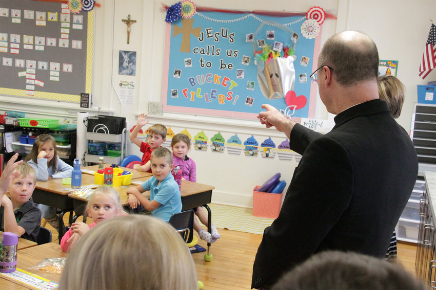 Bishop W. Shawn McKnight calls on a student while taking a tour of St. Martin School in St. Martins on Nov. 20. The school's third-graders wrote to him, inviting him to offer Mass in church and visit them in school.
