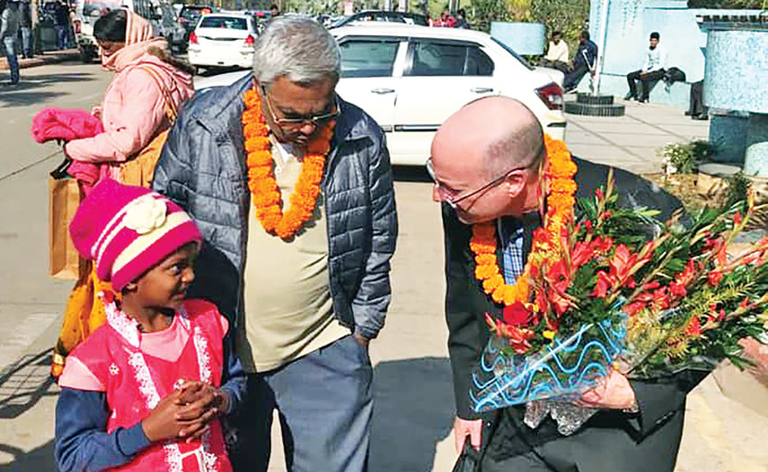 A young parishioner greets Bishop W. Shawn McKnight as he arrives in Kunkuri, India, on pilgrimage to the Diocese of Jashpur on Dec. 28. With them is Father Alex Ekka, a priest of the Jashpur diocese who is serving as pastor of St. Ann parish in Warsaw and the Ss. Peter and Paul mission in Cole Camp.