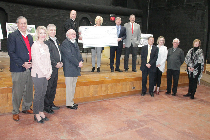 Bishop W. Shawn McKnight joins St. Mary's Hospital Foundation Director Bev Stafford, President Greg Meeker and other members of the foundation's board of trustees in the former Shikles Auditorium in Jefferson City Jan. 31. Ms. Stafford and Mr. Meeker presented the bishop a $200,000 gift from the foundation toward an estimated $4 million renovation of the building, which will serve as the new headquarters for Catholic Charities of Central and Northern Missouri and a center providing help to people in need in the area.
