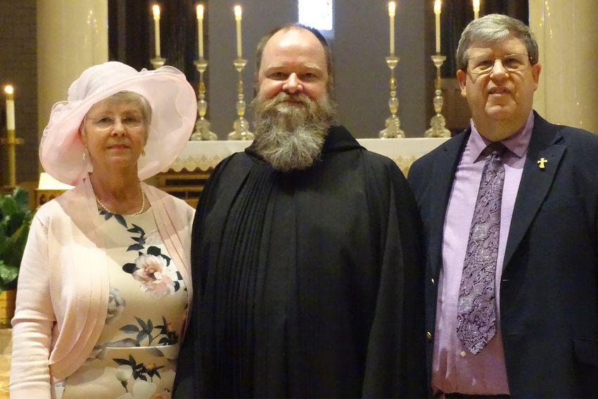 Benedictine Brother Irenaeus Petree stands with his mother, Elaine Thompson, and his stepfather, Deacon David Thompson, in St. Benedict Abbey Church in Subiaco, Arkansas, after professing final vows in the Benedictine order.