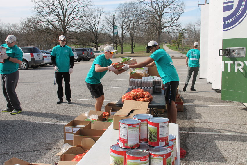 Members of the Frassati Fraternity and their chaplain, Father Joshua Duncan, staff a mobile food distribution center sponsored by the Food Bank of Central & Northeast Missouri and the United Way of Central Missouri.