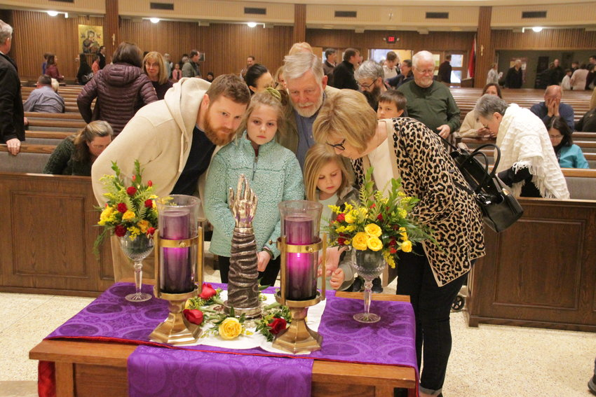 A family examines a major relic of St. Jude the Apostle, consisting of bone fragments of the saint's forearm, encased in an 18th century reliquary, after the closing Mass for the diocesan Day of Prayer for Vocations on March 15 in the Cathedral of St. Joseph.