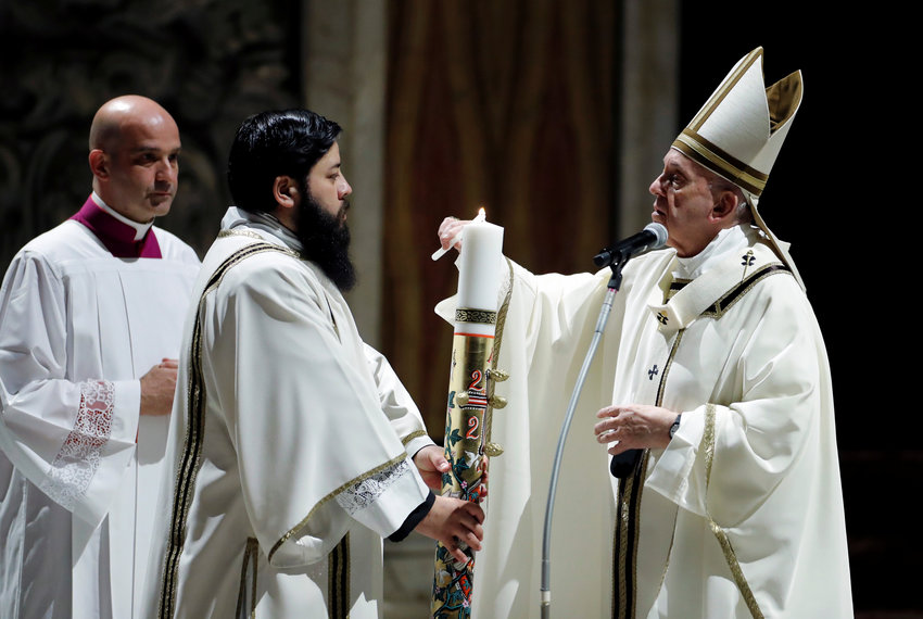 Pope Francis lights the paschal candle at the start of the Easter vigil in St. Peter's Basilica at the Vatican April 11, 2020. The Mass was celebrated without the presence of the public due to the coronavirus crisis.