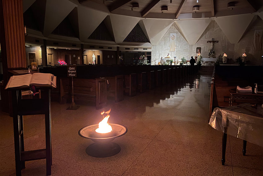 Candles and the Easter fire help illuminate the Cathedral of St. Joseph in Jefferson City, as Deacon Tyler McClay proclaims the Gospel reading during the Easter Vigil on Holy Saturday.