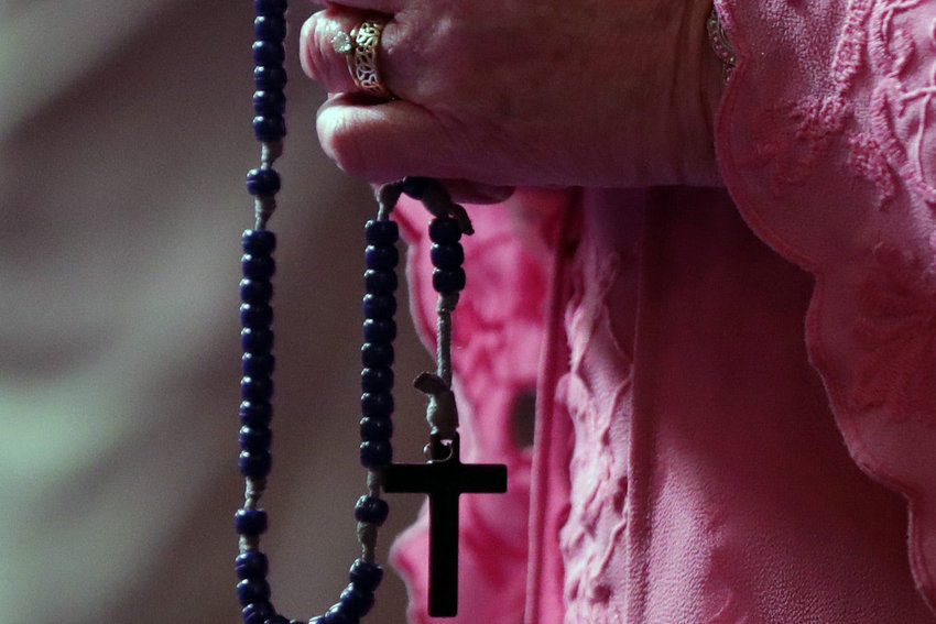 A woman prays with a rosary in 2019 at Old St. Mary's Church in Detroit. In an April 25, letter, Pope Francis asked Catholics to make a special effort in May to pray the Rosary, knowing that by doing so they will be united with believers around the world asking for Mary's intercession in stopping the COVID-19 pandemic.