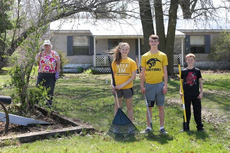Mary Lou Dawson stands six feet from her cheerful neighbor children Megan, Kyle and Cole Hays as they pause for a break from cleaning flower beds and helping with yardwork.