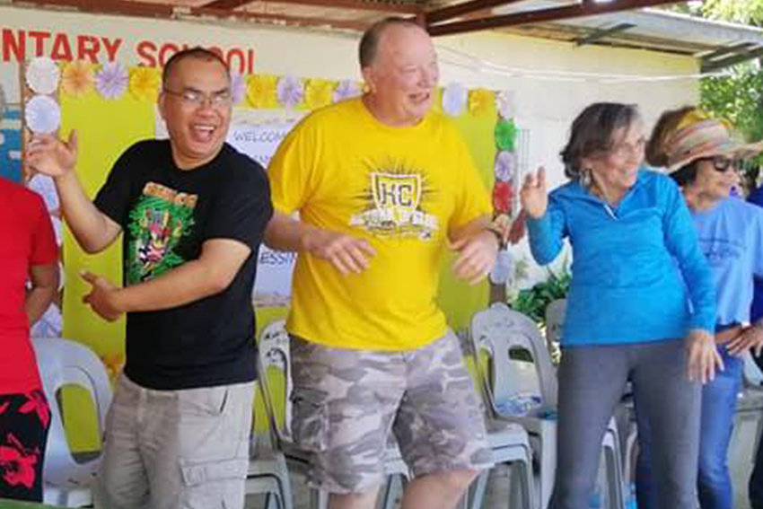 Mark and Carolyn Saucier and Father Dandi Bermejo help celebrate the completion of a new concrete floor, paid for by benefactors from the United States, in the Begonia Elementary School, during a 2020 mission trip to Fr. Bermejo's St. Joseph the Worker Mission on the island of Negros Occidental in the Philippines.