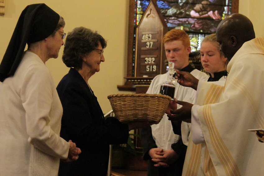 Sister Kathleen Donovan of the School Sisters of Notre Dame, a former principal of St. Thomas the Apostle School, and Sister Rosemary Boessen of the Sisters of Mercy, a St. Thomas native, present the gifts of bread and wine to Father Leonard Mukiibi, administrator of St. Thomas the Apostle parish, during a Mass for the parish's 150th anniversary.