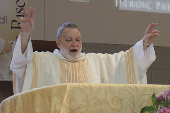 Dominican Father Richard Litzau, who will take up a new assignment in Wisconsin after serving for six years as pastor of St. Thomas More Newman Center parish in Columbia, blesses the people at the end of a Mass in the Newman Center chapel.