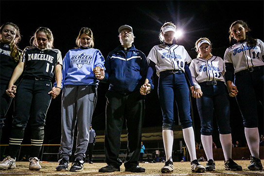 Fr. Mike Coleman leads a prayer following a Class 2 sectional softball game Oct. 17, 2018, at American Legion Park. Tolton defeated Marceline 6-1 to advance to the state quarterfinals. [Hunter Dyke/Tribune file photo]
