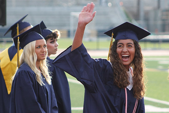 A graduating senior greets her family while entering Helias Catholic High School's Crusader Athletic Complex.