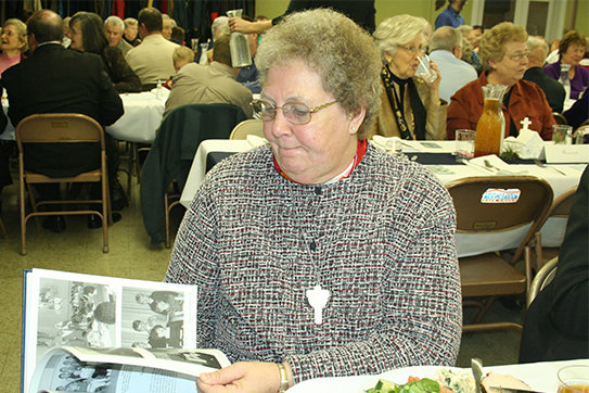 Franciscan Donna Eggering peruses a parish history book during the 150th anniversary celebration for Immaculate Conception parish in Brookfield in 2009.