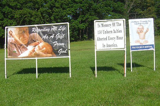 Members of St. Patrick parish in Laurie displayed these banners on the church grounds through May and June, along with 150 white crosses in memory the millions of pre-born babies who have been lost to abortion.