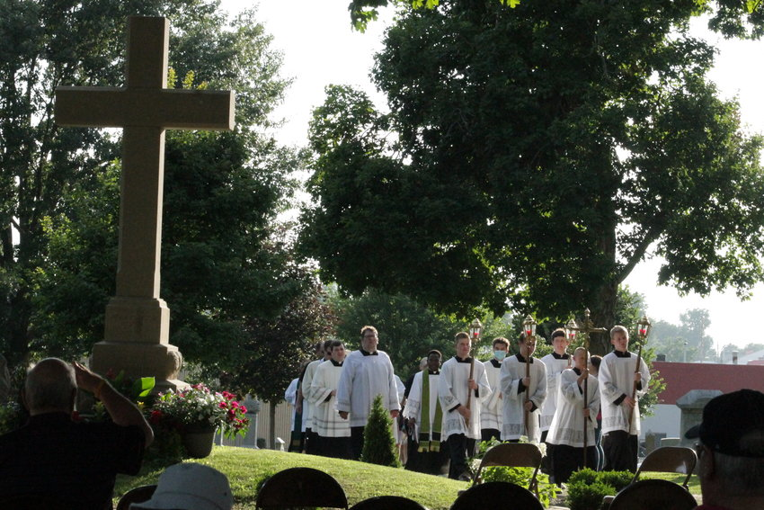 Priests and seminarians of the Diocese of Springfield in Illinois lead a procession to the burial place of Venerable Father Augustus Tolton, a former slave in northeastern Missouri who became the Roman Catholic Church's first recognizably black priest in the United States, on the 123rd anniversary of his death.