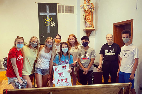 Members of Fr. Tolton Regional Catholic High School's House Executive Council make a surprise visit to Father Michael Coleman on July 17 in Holy Spirit Church in Centralia.