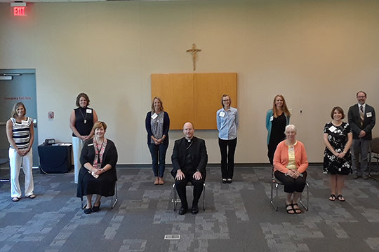 (Front row) Dr. Erin Vader, diocesan superintendent of Catholic schools; Bishop W. Shawn McKnight; Patricia Kirk, principal of St. Joseph School in Westphalia; Sara Hooley, principal of Holy Family School in Hannibal; (back row) Anne Luebbert, principal of Immaculate Conception School in Loose Creek; Julie Mitchem, principal of St. Andrew School in Tipton; Mindy Schneider, principal of Immaculate Conception School in Macon; Erin Polson, principal of St. Peter School in Fulton; Dana Schroeder, principal of Immaculate Conception School in Montgomery City; and Dr. Daniel Everett, president and principal of Fr. Tolton Regional Catholic High School in Columbia, gather for new principal orientation on July 28 in the Alphonse J. Schwartze Memorial Catholic Center in Jefferson City.
