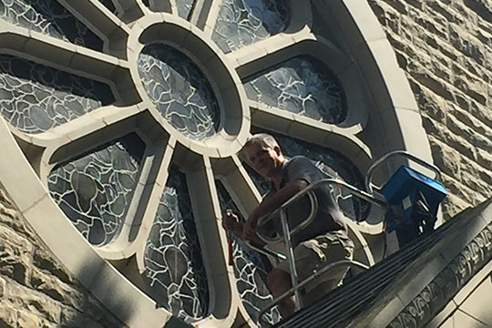 An artisan from Emil Frei & Associates of St. Louis works on restoring the magnificent 12-paned rose window above the entrance to the chapel at the Shrine of Our Lady of Sorrows in Starkenburg. The same company created and installed the window in the early 1900s.