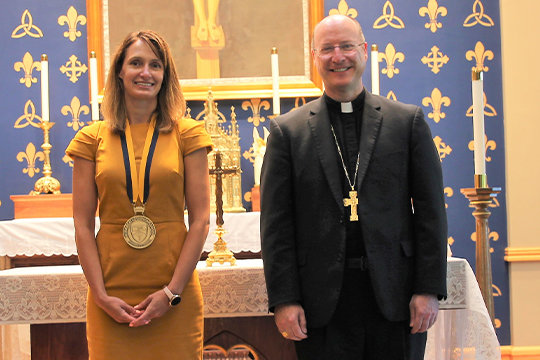 Kenya Fuemmeler, newly installed president and principal of Helias Catholic High School in Jefferson City, displays the medal Bishop W. Shawn McKnight, right, presented to her as a symbol of the office she holds.