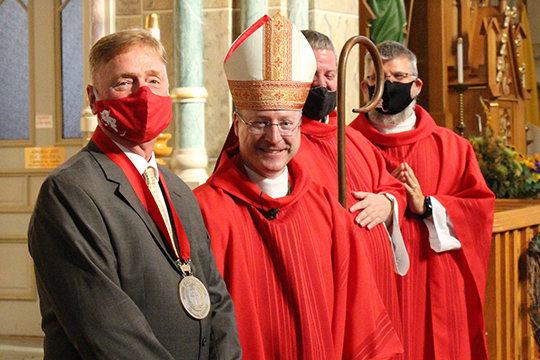 Dr. Mark Register, president of Sacred Heart School in Sedalia, wears the presidential medalion given to him by Bishop W. Shawn McKnight. With them are Father Joseph Corel and Father David Veit, pastors in solidum of St. Vincent de Paul Parish in Pettis County, of which Sacred Heart School is a ministry.