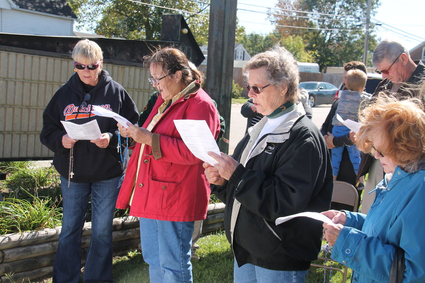 Members of Immaculate Conception and nearby parishes pray the Rosary together at a prominent corner in Owensville during a Public Rosary in the Square observance last October.