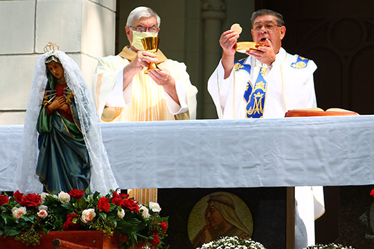 La Salette Father Dennis Meyer elevates the Most Blessed Sacrament during Mass at the Fall Pilgrimage at the Shrine of Our Lady of Sorrows in Starkenburg. With him is Deacon Gerald Korman (left) of Church of the Risen Savior Parish in Rhineland and Monsignor Gregory L. Higley, pastor of St. George Parish in Hermann and of the Rhineland parish.