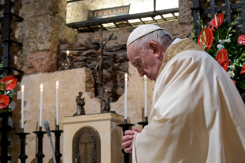 "Pope Francis celebrates Mass at the tomb of St. Francis in the crypt of the Basilica of St. Francis in Assisi, Italy, Oct. 3, 2020. The pope signed his new encyclical, ""Fratelli Tutti, on Fraternity and Social Friendship,"" at the end of the Mass."