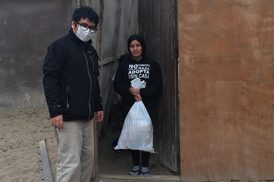 """Father Cesar Anicama, a priest of the Jefferson City diocese who is serving as a Missionary of St. James the Apostle in his homeland of Peru, distributes food baskets to families affected by the COVID-19 pandemic in Villa El Salvador. Fr. Anicama is ministering at Nuestra Señora de la Paz (Our Lady of Peace) parish in Villa El Salvador, about 20 miles south of Lima, the nation's capital. This coastal city is home to about 4 million people, many of whom resettled there after fleeing the poverty of the Andes Mountains almost a half-century ago. He said he remains safe and healthy despite the pandemic, """"thanks be to God."""" He asks the people of the Jefferson City diocese to pray """"for God's healing hand to be placed on the poorest and most abandoned people, and for those who have lost loved ones."""""""