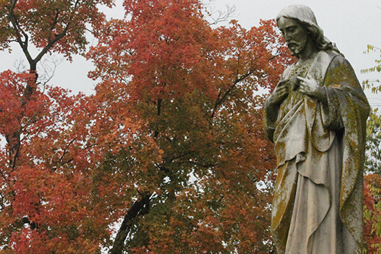 A weathered stone sculpture of the Sacred Heart of Jesus sets apart the autumn colors in St. Peter Cemetery in Jefferson City.