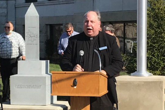 Monsignor Robert A. Kurwicki leads a prayer of dedication for the Cole County Bicentennial Memorial, visible in the background, outside the Cole County Courthouse in Jefferson City. The county was founded Nov. 16, 1820, nine months before Missouri became a state.