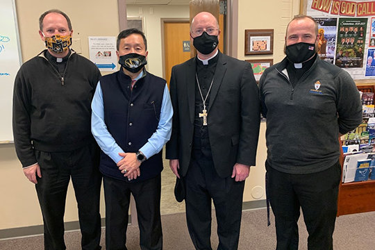 Father Daniel Merz, pastor of St. Thomas More Newman Center parish in Columbia; Dr. Mun Choi, president of the University of Missouri and chancellor of its Columbia campus; Bishop W. Shawn McKnight; and Father Paul Clark, associate pastor, pause for a photo during Dr. Choi's visit to the Newman Center.