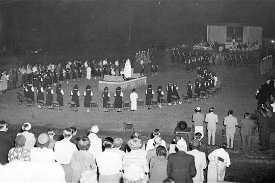 Grade school and high school students from St. George Parish in Hermann participated in the Living Rosary Rally for Peace that was presented in May 1952 at the Hermann City Ball Park. The entire community came together to pray for peace during the Korean War.