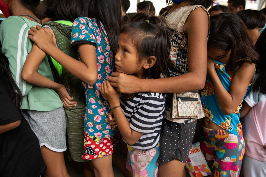Children wait in line for food at an evacuation center in Manila, Philippines, Nov. 14, 2020, after being forced from their homes from flooding caused by Typhoon Vamco. Five tropical storms or typhoons have hit the Philippines in a three-week period, including the strongest typhoon since 2013 and the biggest floods since 2009.