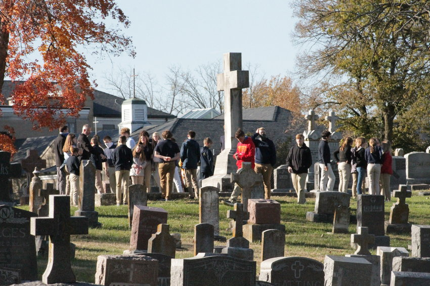 Eighth-graders from St. Peter Interparish School in Jefferson City gather with their teacher and Father Jeremy Secrist around the burial place of Monsignor Joseph Selinger, who was pastor of St. Peter parish for 34 years.