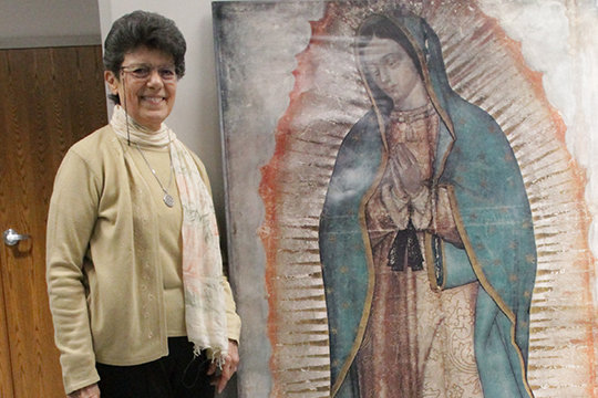 Sister Ana Luisa Prieto Valdés of the Sisters of Charity of the Incarnate Word stands next to a large reproduction of the image of Our Lady of Guadalupe that miraculously appeared on the cloak of St. Juan Diego after the Blessed Mother's apparition to him in 1531. Sr. Ana Luisa gave presentations on Our Lady of Guadalupe in Jefferson City and Columbia in December of 2019.