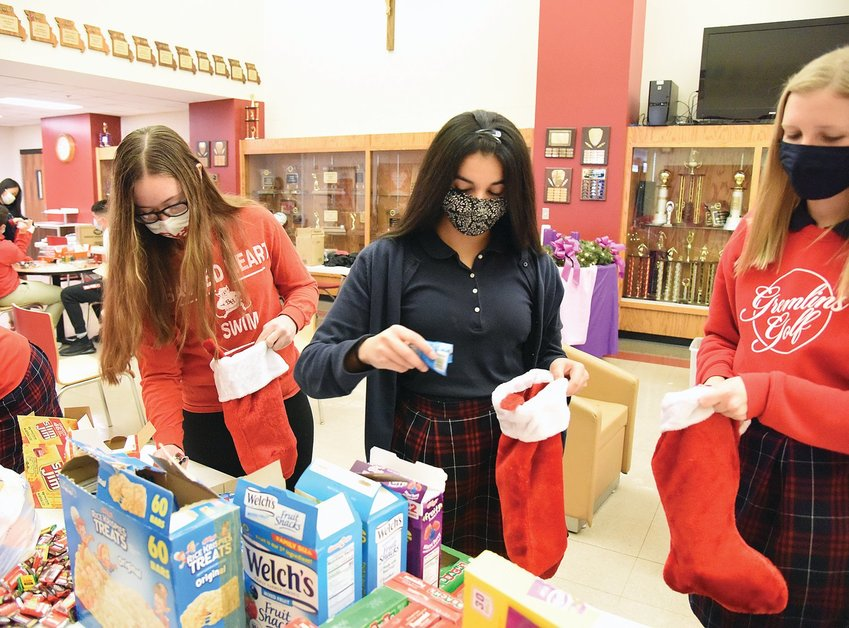 Amelia Schott, left, president of the Sacred Heart Key Club Chapter, and members Tania Bhardwaj, center, and Megan Wingerter place treats into stockings for Whiteman Air Force Base's 509th Military Police Division on Dec. 18. They gave the stockings to military members who couldn't go home for Christmas.