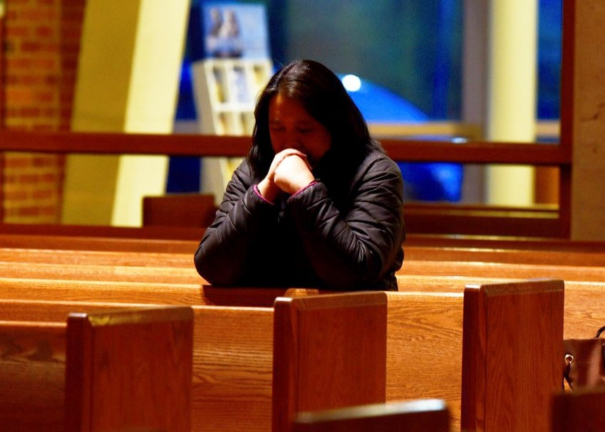 A woman prays alone at St. Leo the Great Church in Fairfax, Va., March 18, 2020.