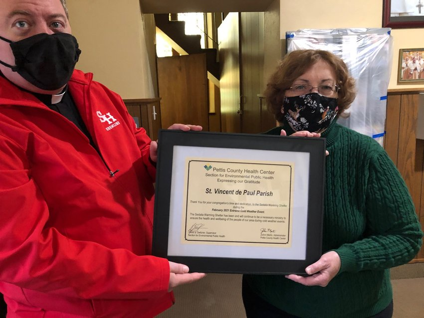Parishioner JoAnn Martin, administrator of the Pettis County Health Center, presents a citation to Father Joseph Corel, pastor in soldium of St. Vincent de Paul Parish in Pettis County, for the parish hosting the city's emergency winter warming shelter for the past two winters.