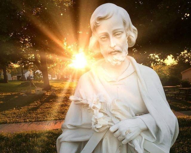 The rising sun illuminates an image of St. Joseph outside St. Joseph Church in Edina.