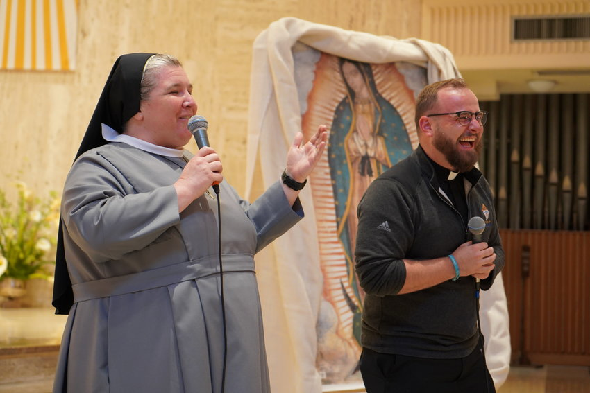 Keynote presenters Sister M. Karolyn Nunes of the Sisters of St. Francis of the Martyr St. George and Father Paul Clark share a funny story during this year's Sixth- and Seventh-Grade Vocation Day.