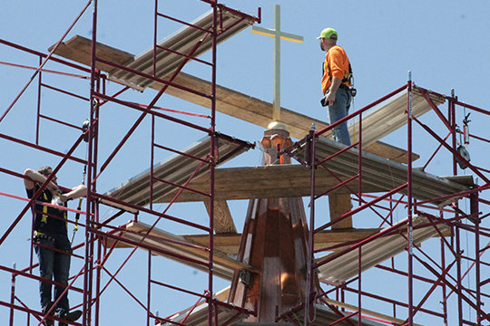 Employees of Renaissance Roofing examine the new cross and copper sheathing on the cupula atop the Cathedral of St. Joseph in Jefferson City April 30. Bishop McKnight blessed the cross before it was lifted into place. Completion on the roof's replacement following last spring's major hail damage will roughly coincide with the bishop's decree restoring the Sunday obligation for the faithful to attend Mass in person.