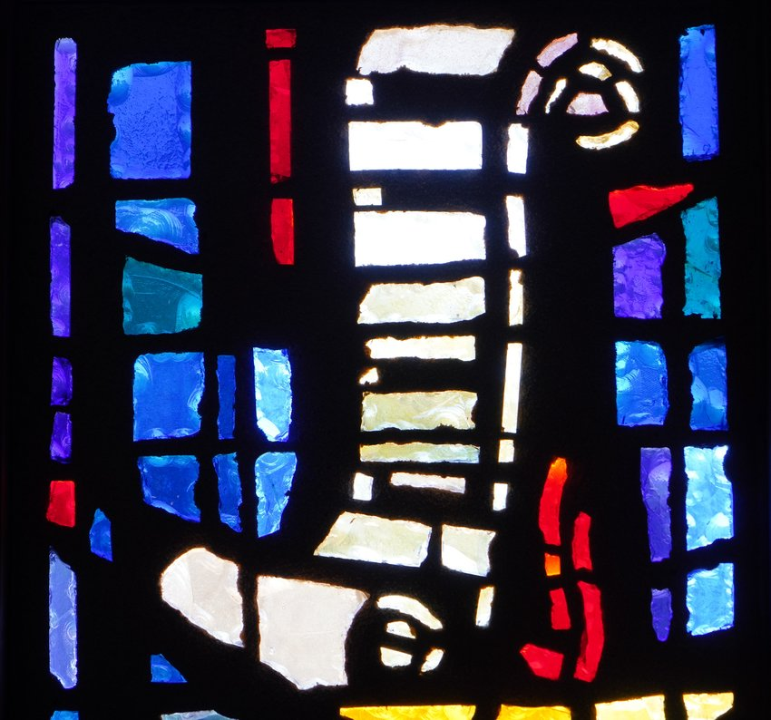 A scroll and lamp, symbolizing the preaching and teaching mission of the Church and its priests, are depicted in stained glass in the chapel of the Cathedral of St. Joseph in Jefferson City.