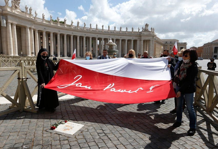 People carry a flag with the name of St. John Paul II over the spot of the May 13, 1981, assassination attempt against the Polish pope, in St. Peter's Square at the Vatican May 13, 2021. Cardinal Stanislaw Dziwisz, the former secretary of St. John Paul II, and a small group of Catholics gathered in the square to mark the 40th anniversary of the shooting.