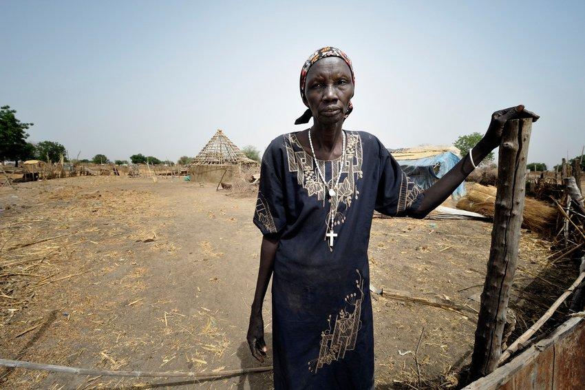 """Bruna Maloal, una catequista católica de 63 años, se para frente a la puerta de su casa en Abyei, a lo largo de la frontera entre Sudán y Sudán del Sur, en esta foto de archivo del 27 de febrero de 2013. En un documento publicado el 11 de mayo de 2021, el papa Francisco instituyó el """"ministerio de catequista."""""""