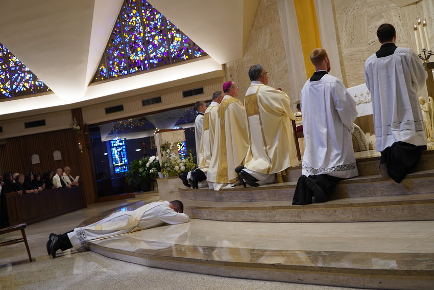 Father Derek Hooper lays prostrate before the altar in the Cathedral of St. Joseph in a gesture of obedience and total reliance on God, while the choir and congregation chant the Litany of Saints during his Ordination to the Holy Priesthood on June. 5.