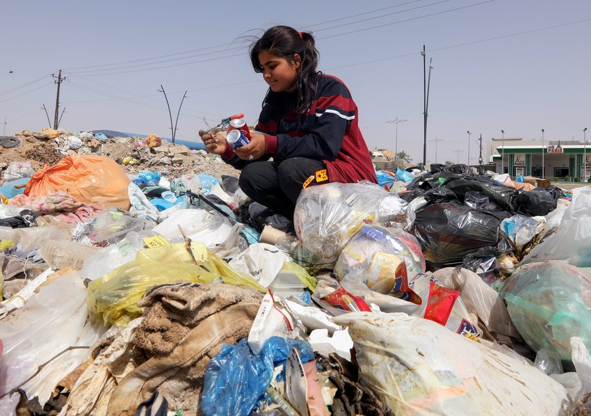 Sahar Shaaban, 11, an Iraqi girl who provides for her family, collects cans from a garbage area in Kirkuk, Iraq, April 21, 2021.