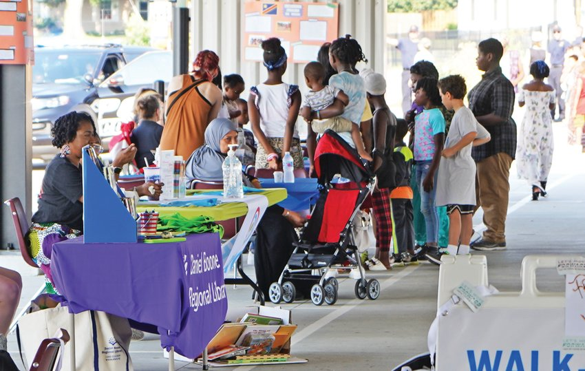 """Participants in the 2021 World Refugee Day celebration gather around tables and booths under the MU Healthcare Pavilion in Clary-Shy Park in Columbia. The theme for the event was """"Together, we heal, learn and shine."""""""
