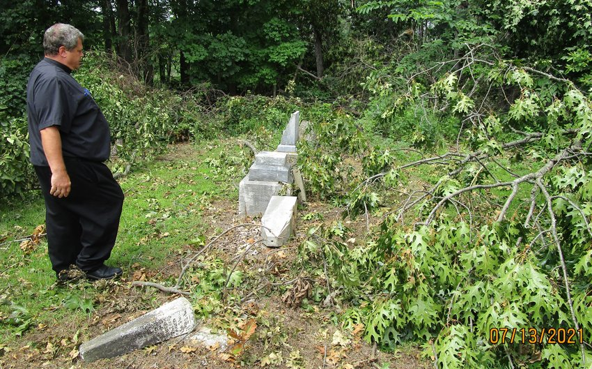 Father Gregory Oligschlaeger VF, pastor of Holy Rosary Parish in Monroe City and St. Stephen Parish in Indian Creek, surveys tree and headstone damage in the St. Peter Cemetery in Brush Creek following a July 9 thunderstorm.