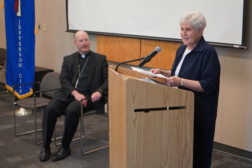 Bishop W. Shawn McKnight listens to Sr. Kathleen address the people who had gathered in the Alphonse J. Schwartze Memorial Catholic Center in Jefferson City to watch her receive the award.